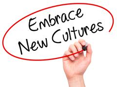 Man Hand writing Embrace New Cultures with black marker on visual screen Stock Photos