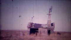 1956: Farm house ruins of windmill and weather worn barn. Stock Footage