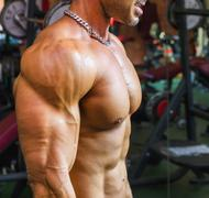Bodybuilder working out at gym, side view of muscular chest, pecs, arms - stock photo