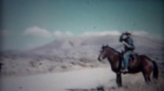 1956: Cowboy tips hat riding horse in western mountain range. Stock Footage