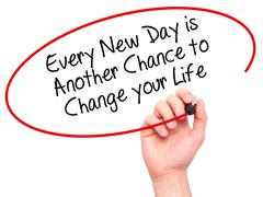 Man Hand writing Every New Day is Another Chance to Change your Life with bla - stock photo