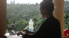 Young entrepreneur typing on her laptop with rain forest in background Stock Footage