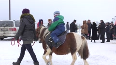 Children ride pony horse as part of winter entertainment activity. Panorama. 4K Stock Footage