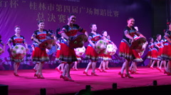 Women dressed in traditional minority clothing dance on stage in China Stock Footage
