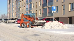 Stock Video Footage of Compact bulldozer push snow from road and parking. 4K