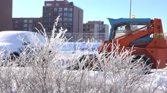 Bushes covered with frost and compact machine clean snow in parking. 4K - stock footage