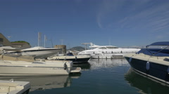Yachts and other sailboats moored in Saint-Tropez's harbor on a sunny day Stock Footage