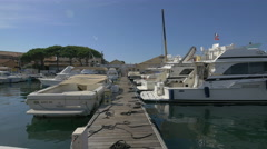 Yachts moored along a dock in Saint-Tropez's harbor Stock Footage