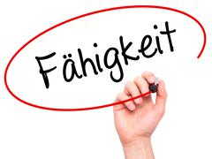 Man Hand writing Fahigkeit (Ability in German) with black marker on visual sc Stock Photos