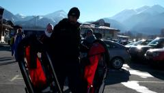 Vacationers at the ski resort come back after a day on the ski resort parking Stock Footage