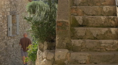 Man walking on a narrow street, passing by stone stairs, in Tourrettes-sur-Loup Stock Footage