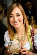 Girl drinking beer at Oktoberfest - stock photo
