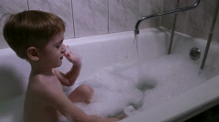 The little boy bathes in a bath with foam - stock footage