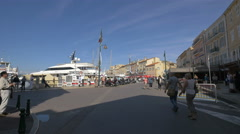 People walking on Quai Suffren, on a sunny day in Saint-Tropez's port Stock Footage
