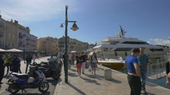 Tourists walking on Quai Suffren, on a sunny day in Saint-Tropez's port Stock Footage
