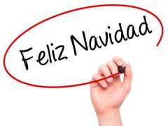 Man Hand writing Feliz Navidad  (Merry Christmas In Spanish) with black marke Stock Photos