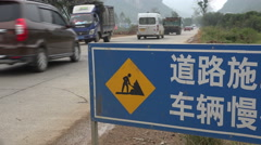China infrastructure, warning sign of road traffic ahead - stock footage