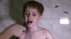 Little boy brushing his teeth, mom helps him - stock footage
