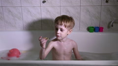 A little boy bathes and plays in the bathroom - stock footage