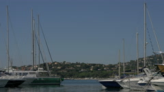 View of boats and a hill with houses in Sainte-Maxime, France Stock Footage