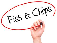 Man Hand writing Fish & Chips with black marker on visual screen Stock Photos