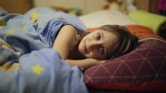 The girl is lying in bed before going to sleep Stock Footage