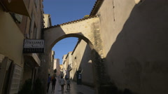 People walking on Rue Miséricorde, under a connecting arch, in Saint-Tropez Stock Footage