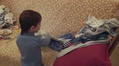 Boy puts clothes Stock Footage