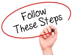 Man Hand writing Follow These Steps with black marker on visual screen - stock photo