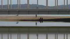 Group of tourists relaxing under Sainte-Maxime Bridge, France Stock Footage