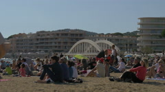 Boys walking and tourists relaxing on the beach near Sainte-Maxime Bridge Stock Footage