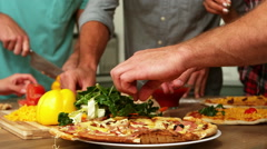 Smiling friends making pizza together Stock Footage