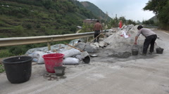 Construction workers rebuild a damaged road in the countryside in China - stock footage