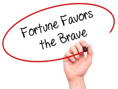 Man Hand writing Fortune Favors the Brave with black marker on visual screen - stock photo