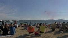 Tourists sitting on the beach and watching the air show in Sainte-Maxime, France Stock Footage