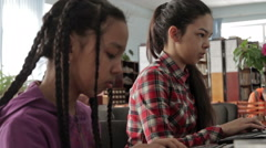Two sisters with long hair in school library Stock Footage
