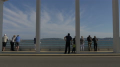 Tourists watching a helicopter flying from the Sainte-Maxime Bridge , France Stock Footage