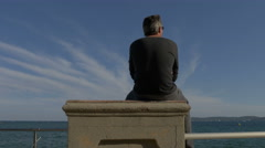 Man sitting on a stone bench on the seafront in Sainte-Maxime, France Stock Footage