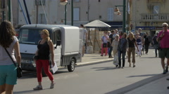 Tourists walking, relaxing and riding scooters in the port of Saint-Tropez Stock Footage