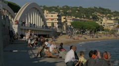Tourists relaxing on the seashore close to Sainte-Maxime Bridge, France Stock Footage