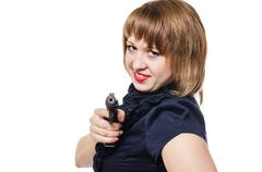The dangerous young woman with long hair shoots from the pistol - stock photo