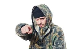 The man in a camouflage points a finger forward - stock photo