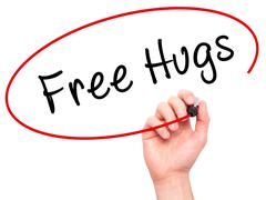 Man Hand writing Free Hugs with black marker on visual screen - stock photo