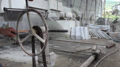 Chinese marble factory, man carefully operates cutting machine - stock footage