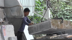 Worker lifts a heavy piece of marble with a crane, in a factory in China Stock Footage