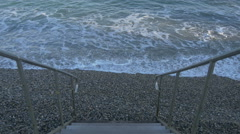 Waves reaching the seashore near a small wooden staircase in Sainte-Maxime Stock Footage
