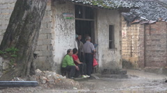 Asia, rural China, people hide in small building from heavy rain Stock Footage