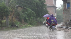 People ride motorbikes through a small village with heavy rain in China Stock Footage