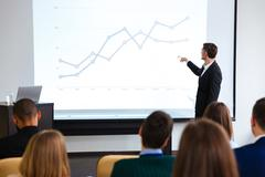 Confident speaker giving public presentation using projector Kuvituskuvat