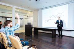 Confident speaker talking to audience on business training - stock photo